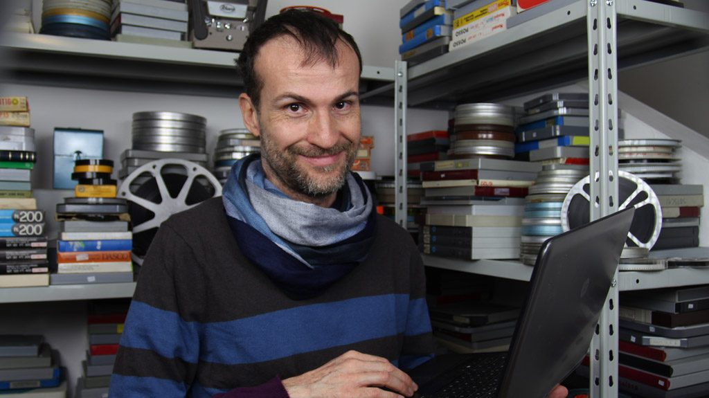 Daniele Carrer with his laptop in front of his 8 mm films collection